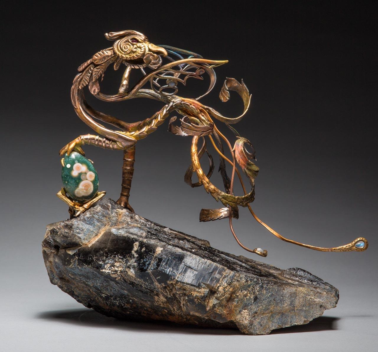 metal sculpture: phoenix on rock